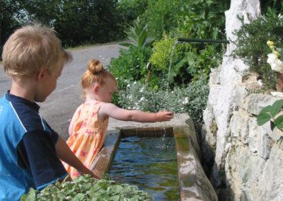 Kinder spielen mit Wasser vorm Brunnen bei Urlaub am Bauernhof Grabenhofer