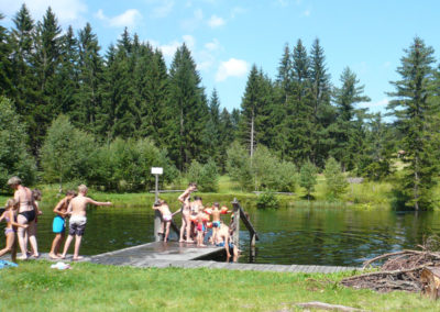 Kinder gehen im Teich schwimmen